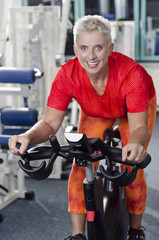 Reife Frau im Fitness Studio an Trainingsrad Spinner