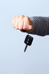 Hand holding car keys isolated on gray background