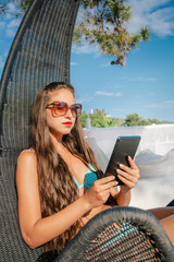 Beautiful girl working on the tablet at the beach
