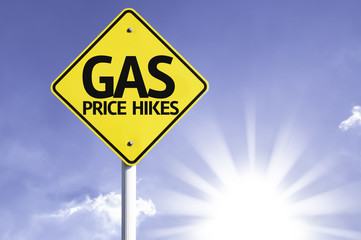 Gas Price Hikes road sign with sun background