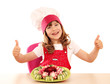 happy little girl cook with thumbs up and decorated salad