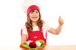 happy little girl cook with thumb up and decorated salad