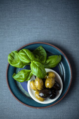 Fresh basil leaves with a bowl of olives