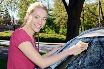 Twen wischt Autoscheibe mit Fenster-Leder