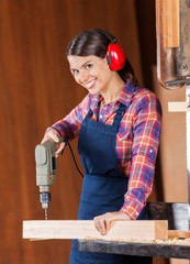 Female Carpenter Using Drill Machine On Wood