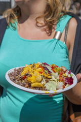 Busty girl showing tasty paella with Mediterranean salad