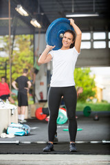 Fit Woman Lifting Barbell Plate
