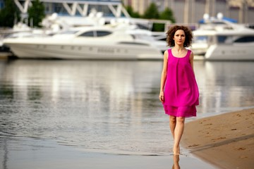 Young woman in a red dress and curly hair on the water coast