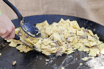 Chef cooks Ravioli pasta with porcini mushrooms