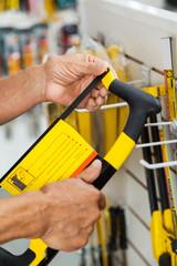 Salesman Examining Hacksaw In Store