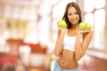 Beautiful young woman with green apples on interior background