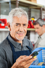 Confident Senior Salesman Holding Tool In Store