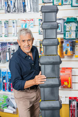 Confident Senior Man Stacking Toolboxes In Store