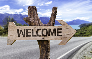 Welcome wooden sign with a street background