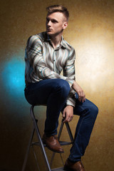 Portrait of handsome stylish man in trendy clothing sitting on l
