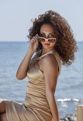 Italy, portrait of a beautiful girl with sun glasses by the sea
