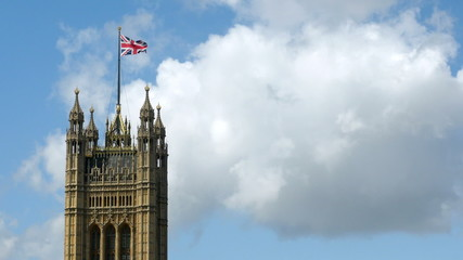 Union Flag flying over UK parliament building.