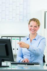 geschäftsfrau zeigt auf den computerbildschirm
