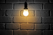 Light bulb turn on in room with brick wall