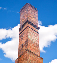 Close up brick chimney on the roof with cloudy blue sky backgrou