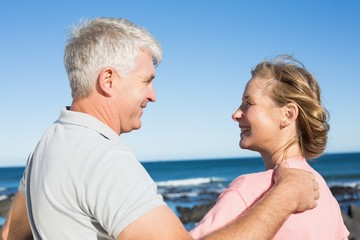 Happy casual couple smiling at each other by the coast