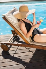 Beautiful woman holding drink by swimming pool