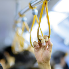 people holding onto a handle on a train