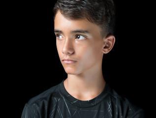 Serious hispanic teenage boy isolated on black