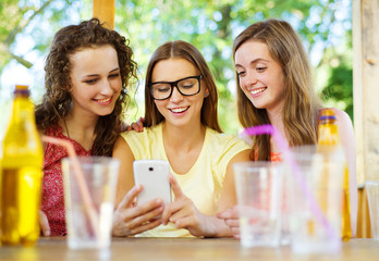 Girls having fun with smartphone in pub
