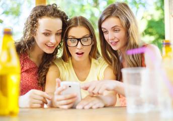Girls having fun with smartphone in pub