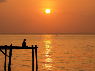 Meditation man on wooden pier under sunset sea
