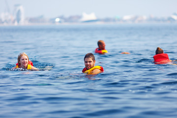 people in lifejackets swimming in open sea