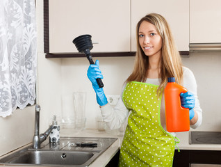 woman with plunger and detergent in kitchen