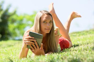 girl lying on grass enjoying reading  ereader