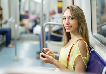 Girl with smartphone in metro