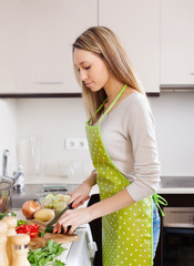 Blonde girl in apron cooking with vegetables