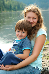 happy mother and son near the river