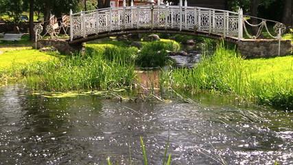 River water stream flow under white decorative bridge in park