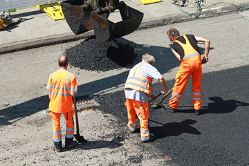 Straßenbauarbeiter mit Schaufeln