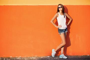 teenage girl leaning against orange wall in urban environment