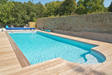 Fototapety Summer outdoor swimming pool with green trees.