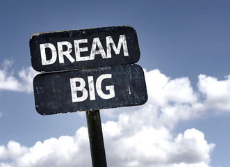Dream Big sign with clouds and sky background