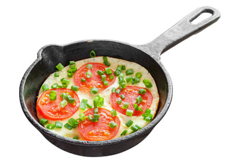 frying pan with scrambled eggs and tomatoes