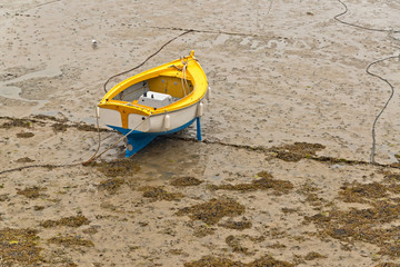 Small boat in harbor of Erquy on sand at ebb-tide with cloudy sk