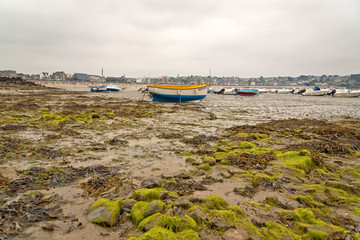 Boats in harbor of Erquy on sand at ebb-tide with cloudy sky. Br