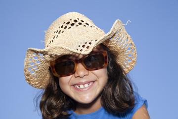 Niña con gafas de sol y sombrero de paja