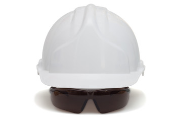 Construction helmet and safety goggles on white background