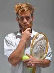 young bearded man with tennis racket and ball