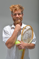 young bearded man smiling with tennis racket and ball