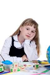Beautiful schoolgirl sits at a school desk on a white background